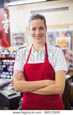 Happy pretty woman looking at camera with arms crossed at supermarket