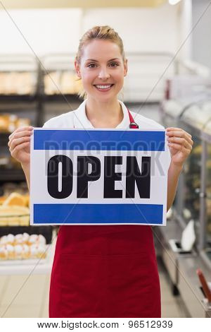 Portrait of a smiling blonde woman holding a sign in bakery