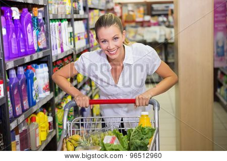 Portrait of smiling woman walking in aisle with his trollet at the supermarket
