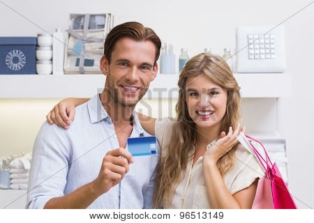 Portrait of a happy couple showing their new credit card at the mall