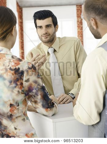 Portrait of young businessman talking to colleagues.