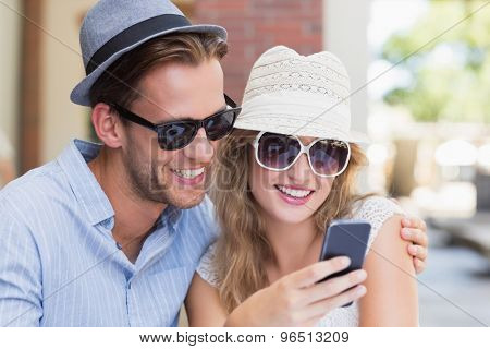 Cute couple looking at their smartphone at the cafe terrace