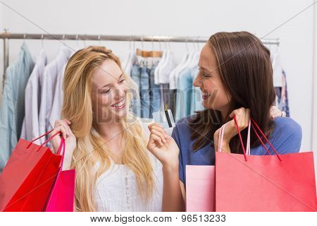 Friends holding a credit card while carrying shopping bags