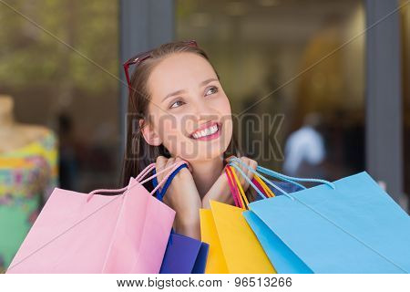 Happy woman carrying shopping bags and looking away