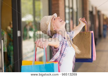 Side view of a carefree woman holding shopping bags