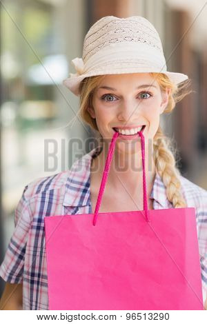 Excited blonde woman with shopping bag in her mouth