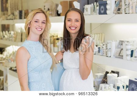 Happy women smiling at camera and holding bottle of perfume in a beauty salon