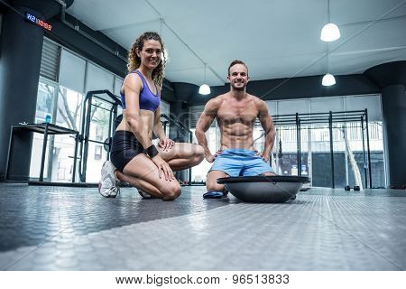 Portrait of a muscular couple with a bosu ball