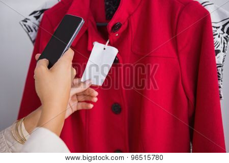 Woman taking a photo of price tag at a boutique
