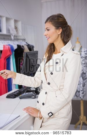 Smiling woman paying by credit card at a boutique