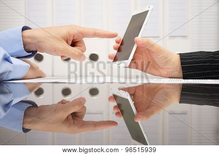 Businesswoman On Meeting Shows  Results On Smart Mobile Phone To Partner, He Is Pointing To Specific
