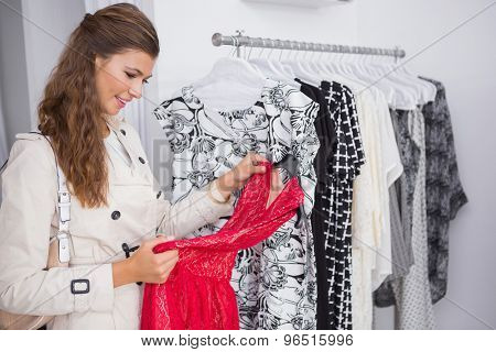 Smiling woman looking at red dress at a boutique