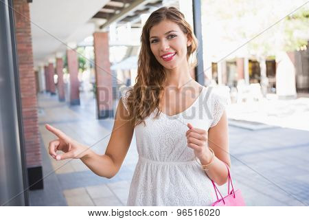 Portrait of smiling woman pointing the window and looking at camera at the shopping mall