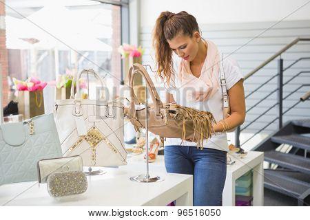 Smiling woman looking at handbag at a fashion store
