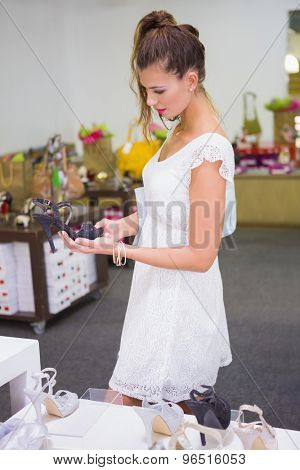 Smiling woman looking at high-heeled sandals at a shoe shop
