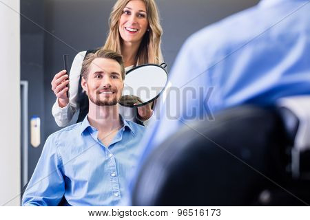 Haircutter showing customer the new cut