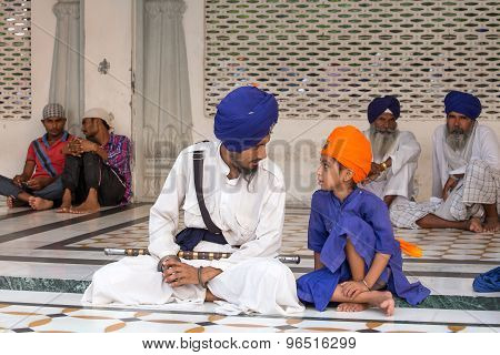 Sikh Man And Boy Visiting The Golden Temple In Amritsar, Punjab, India.