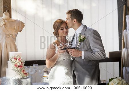 Young bride and groom kissing after toast