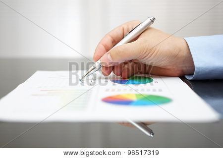 Closeup Of Malel Hand Analyzing Business Report On Black Desk