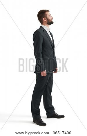 full length portrait of businessman in formal wear looking up. isolated on white background