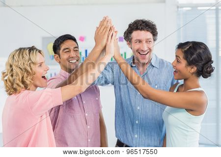 Casual business team high fiving in the office