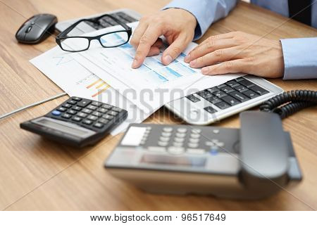 Businessman Is Reviewing Report On His Full Desk
