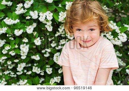 Outdoor close up portrait of adorable little blond boy of 4 years old with hairstyle and sweet smile