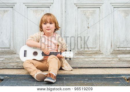 Little happy boy plays his guitar or ukulele, sitting by the wooden door outdoors