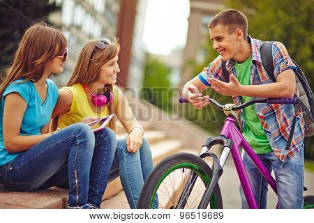 Happy guy on bicycle talking to pretty girls outside