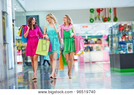 Beautiful girlfriends with paperbags shopping together