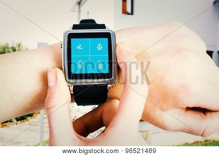 Woman using smartwatch against home automation system
