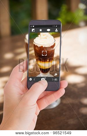 Female hand holding a smartphone against chocolate sundae with whipped cream and chopped nuts