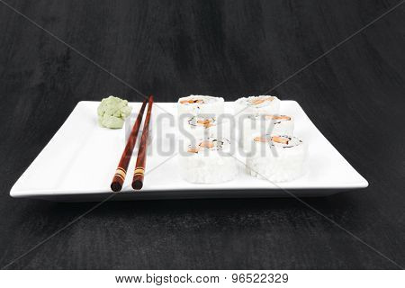 Maki Sushi - California Roll made of Fresh raw Salmon, Cream Cheese and Avocado inside. Served with wasabi . over black table . on square white plate