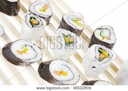 Maki Rolls and California rolls made of fresh raw Salmon, Tuna and Eel with Cream Cheese and Avocado . Isolated over white background . on wooden grid . Maki Sushi and Nigiri