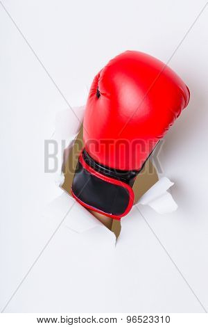 Hand break through paper with red boxing gloves