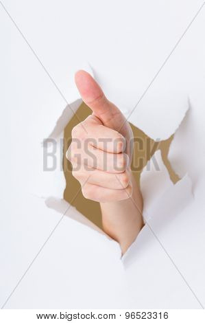 Hand break through paper with thumb up gesture