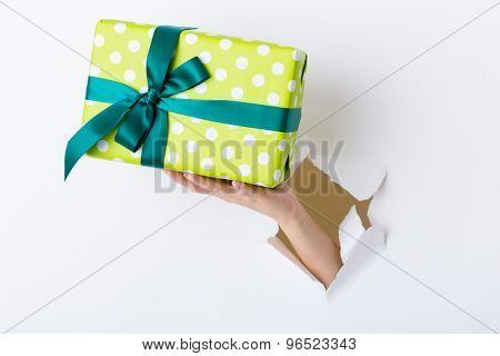 Hand break through paper with green present box