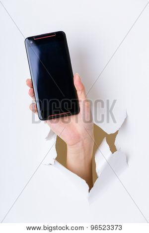Hand break through paper and hold with blank screen of cellphone