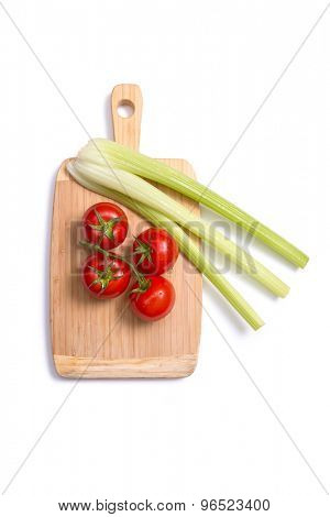 Fresh tomatoes and celery sticks on chopping board, top view isolated on white background