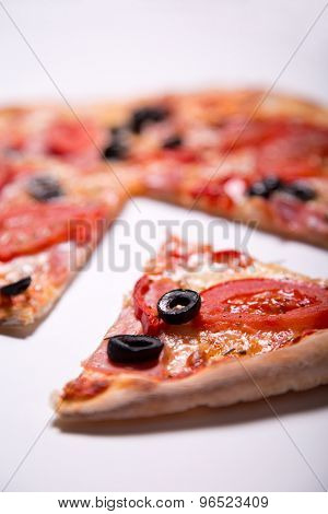 Italian pizza with ham, tomatoes and olives with a slice removed, selective focus on slice