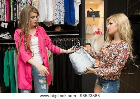 Friends are seeking for a dress at the clothes shop