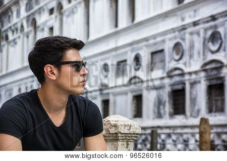 Young Man on Bridge Over Narrow Canal in Venice