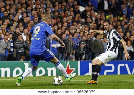 LONDON, ENGLAND. September 19 2012 Chelsea's  Fernando Torres runs with the ball at Juventus's  Stephan Lichtsteiner during the UEFA Champions League football match between Chelsea and Juventus