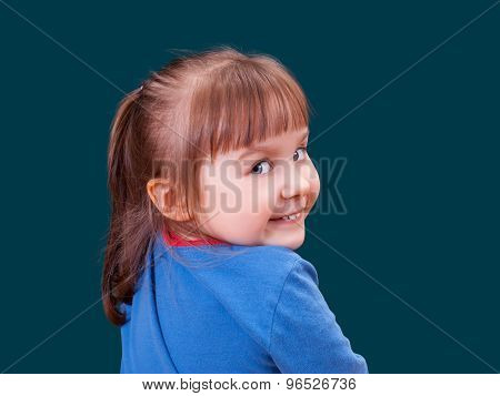 Portrait Of Happy Turning Around And Smiling Little Girl On Dark Green Background. Cheerful Kid.