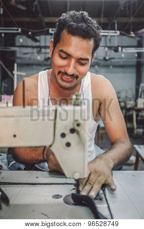 MUMBAI, INDIA - 12 JANUARY 2015: Indian worker sews in clothing factory in Dharavi slum. Post-processed with grain, texture and colour effect.