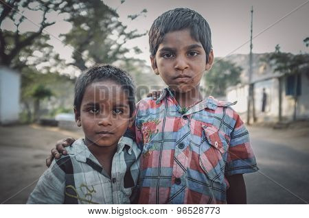 HAMPI, INDIA - 31 JANUARY 2015: Two Indian boys hug in street. Post-processed with grain, texture and colour effect.