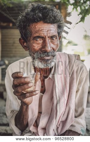 HAMPI, INDIA - 31 JANUARY 2015: Elderly Indian man holds a glass of chai. Post-processed with grain, texture and colour effect.