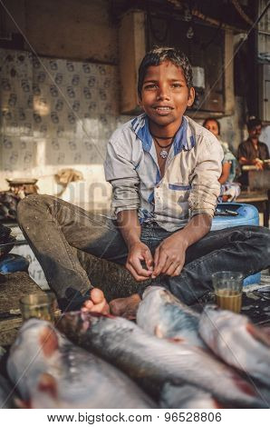 MUMBAI, INDIA - 08 JANUARY 2015: Young worker on a fishmarket next to Dhobi ghat posing while waiting for customers.