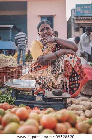 KAMALAPURAM, INDIA - 02 FABRUARY 2015: Indian lady sells vegetables on a market close to Hampi. Post-processed with grain, texture and colour effect.