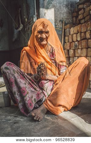 GODWAR REGION, INDIA - 13 FEBRUARY 2015: Elderly Indian woman in sari with covered head sits in doorway of home. Post-processed with grain, texture and colour effect.